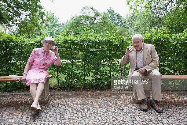 senior man and woman speak to each other on tin can phones in park - beige suit stock pictures, royalty-free photos & images