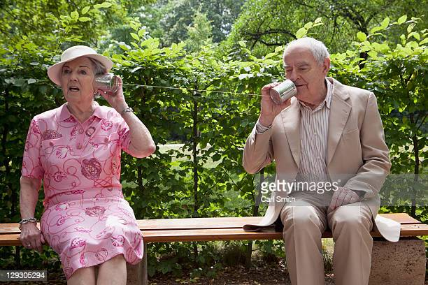 Senior man and woman speak to each other on tin can phones on bench in park