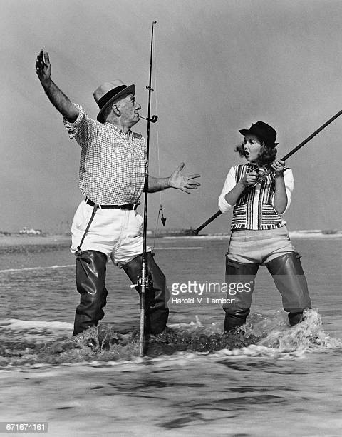 senior man and woman talking while fishing on beach - {{ collectponotification.cta }} foto e immagini stock
