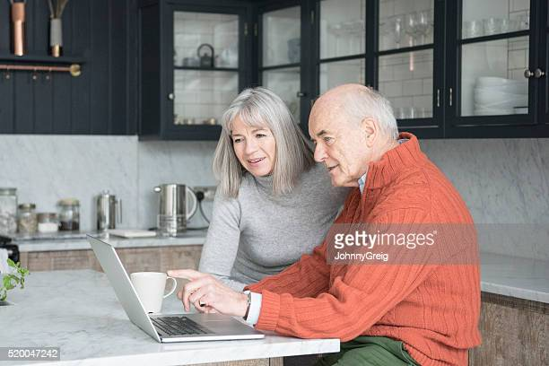 Senior man and woman using laptop at home together