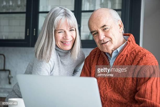 Senior hombre y mujer usando portátil Sonriendo