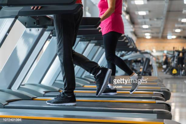 senior man and woman walking over treadmill machines - old man feet stock pictures, royalty-free photos & images