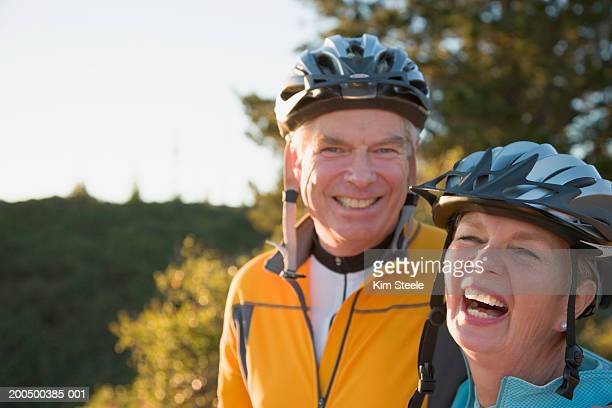 Senior man and woman wearing bicycle helmets, laughing, portrait