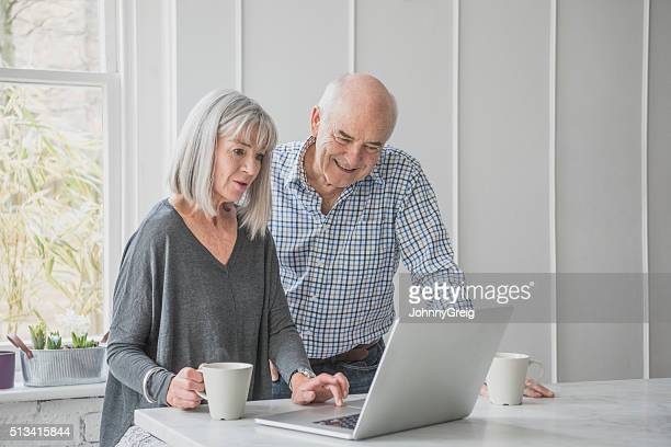 Senior man and woman with laptop and coffee