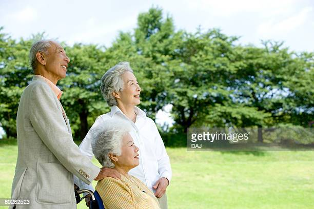 Senior man and women in the field, smiling and looking up