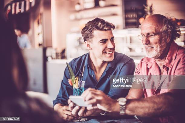 Senior Man and Young Friends Using Smart Phone in Bar, Europe