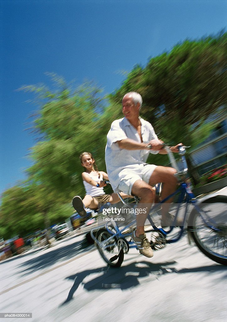 Senior man and young girl riding bikes, blurred motion : Stockfoto