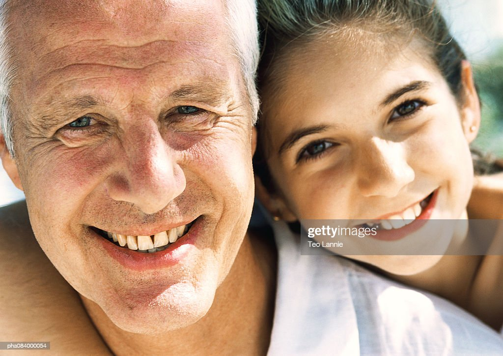 Senior man and young girl smiling, close up portrait. : Stockfoto