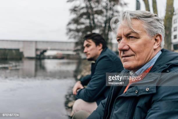 Senior man and young man at the riverside