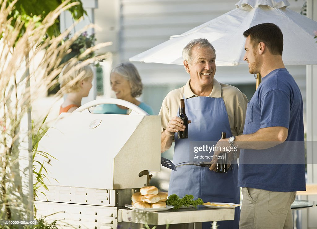 Senior Man and Young Man drinking Beers and Grilling : Foto stock