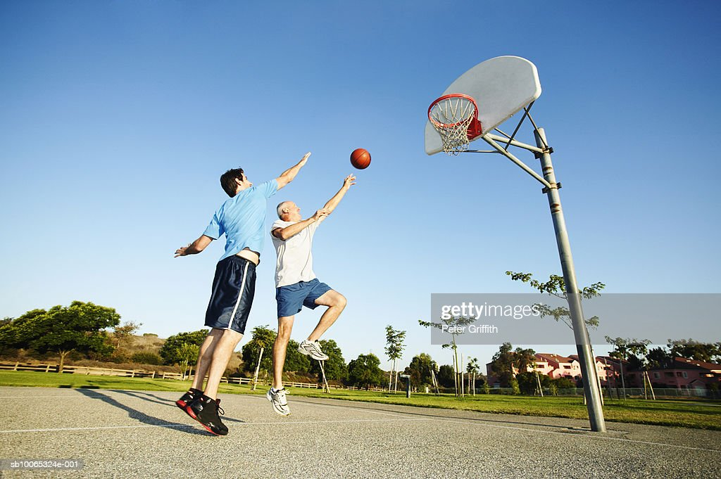 Senior man and young man playing basketball on outdoor court : Foto stock