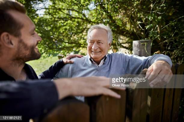 senior man and young man talking at wooden fence in garden - hand auf der schulter stock-fotos und bilder