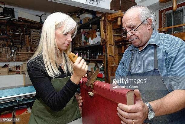 Senior man and young woman applying gold leaf to book spine in traditional bookbinding workshop