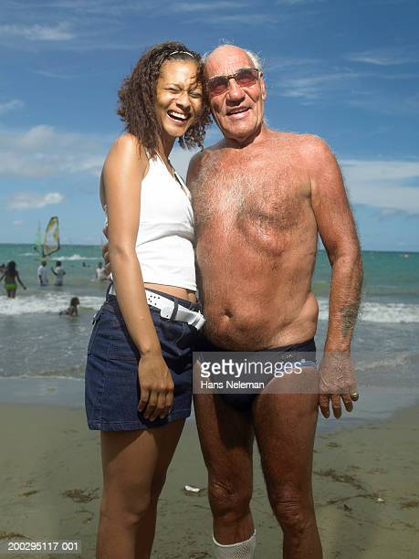 senior man and young woman on beach, portrait - old man in speedo stock photos and pictures