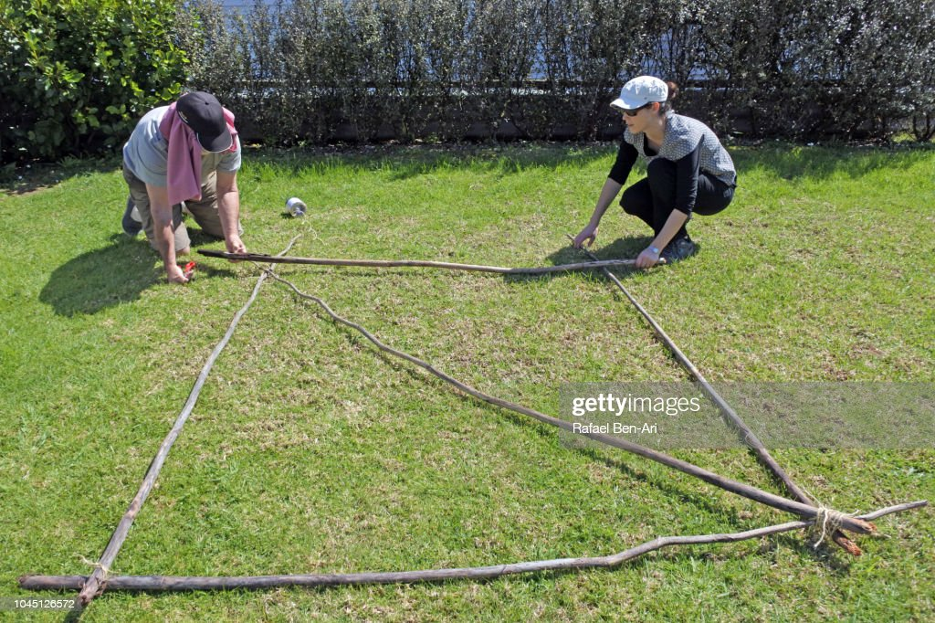 Senior Man and Young Woman Tying Knots Pieces of Wooden Poles : Stock Photo
