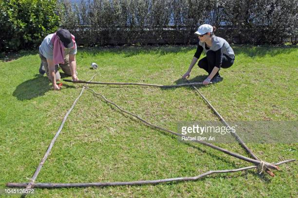 Senior Man and Young Woman Tying Knots Pieces of Wooden Poles