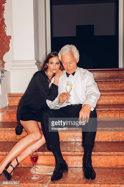 senior man and young woman with glasses of champagne on stairs - may december romance stock photos and pictures
