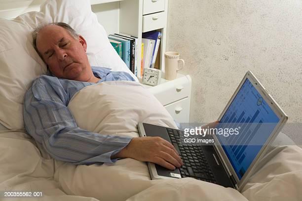 Senior man asleep in bed, holding laptop, close-up
