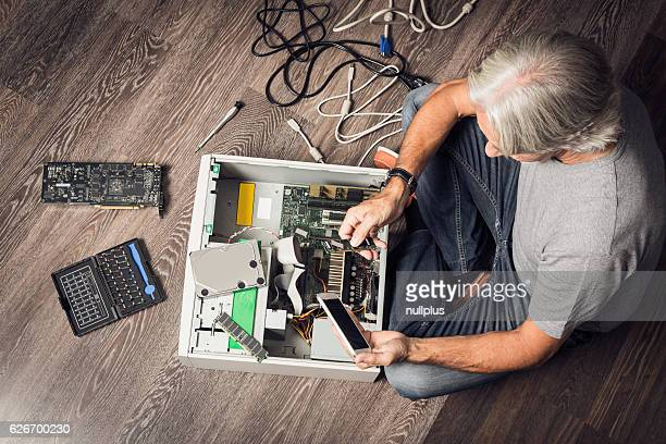 Senior man assembling a desktop computer