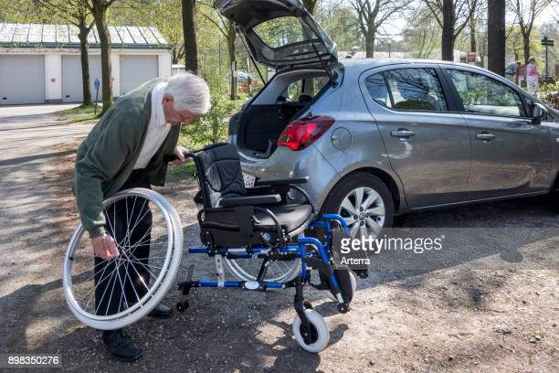 Senior man assembling / dismantling wheelchair from physically disabled elderly wife in front of car at parking