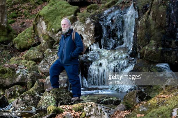 senior man at a frozen waterfall - johnfscott stock pictures, royalty-free photos & images