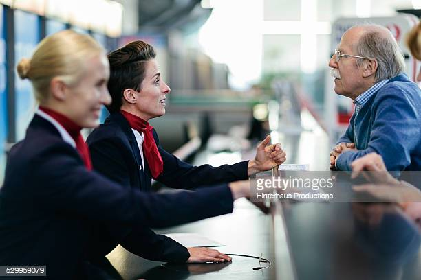 Senior Man At Airport Check-In Counter