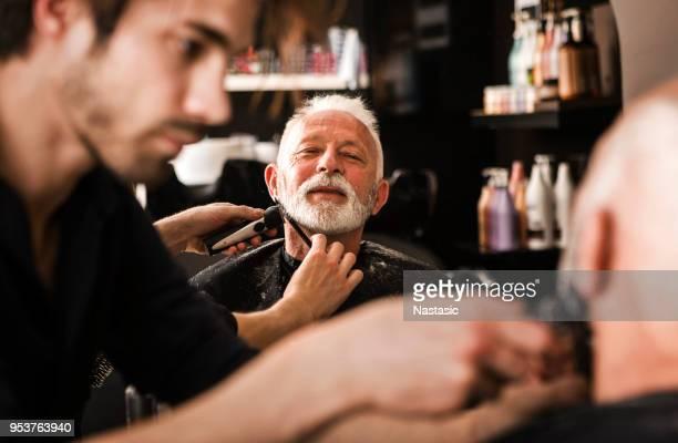 Senior man at barber getting beard trimmed