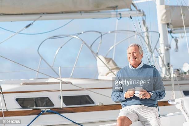 Senior man at boat dock on yacht drinking coffee