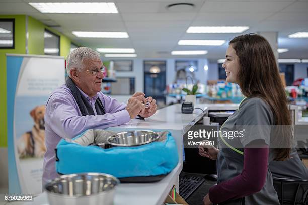 Senior man at counter talking to shop assistant in pet shop