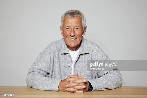 Senior man at desk, smiling, portrait, close-up