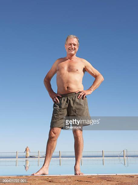 Senior man at edge of pool, hands on hips, portrait, low angle view