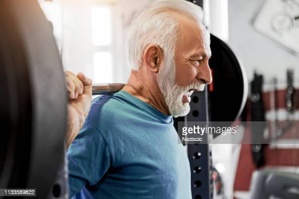 senior man at fitness center working with weight - center athlete stock pictures, royalty-free photos & images
