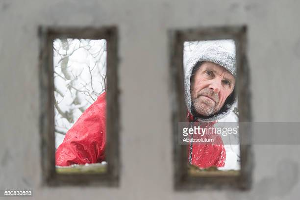 Senior Man at Great War's Bunker Porthole , Snowing, Alps, Europe