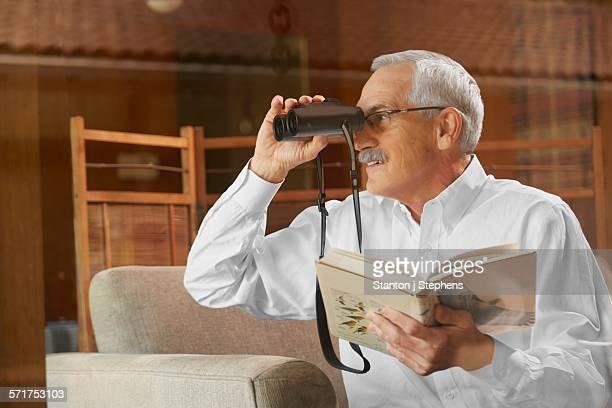 Senior man at home, birdwatching through window, using binoculars
