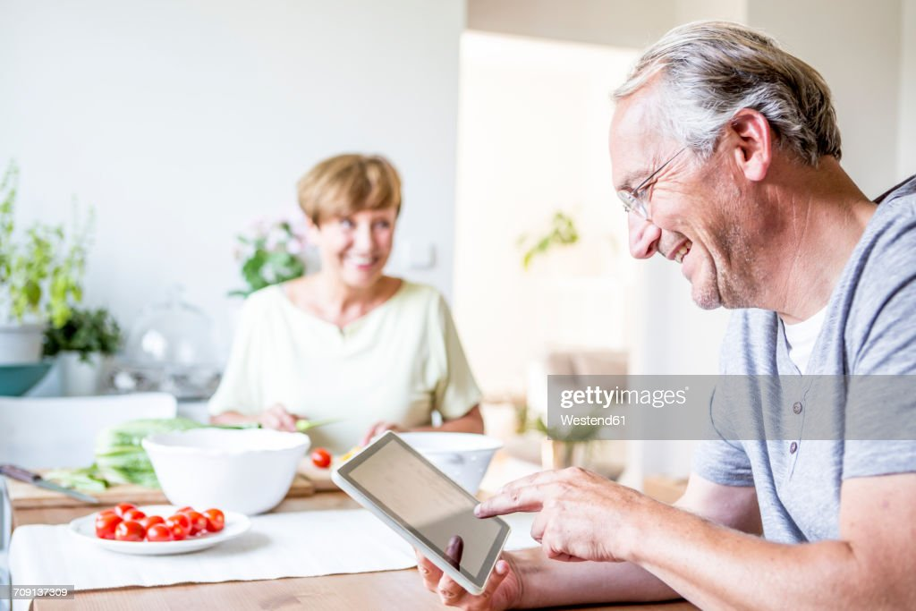 Senior man at home using digital tablet with woman preparing salad in background : Photo