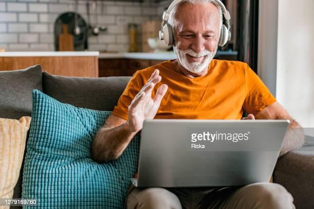 hogere mens thuis die laptop gebruikt - alleen seniore mannen stockfoto's en -beelden