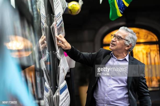 senior-mann am auf der suche nach den nachrichten am kiosk - one night stand stock-fotos und bilder