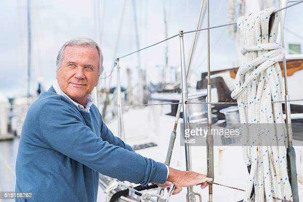 Senior man at marina, standing next to his yacht