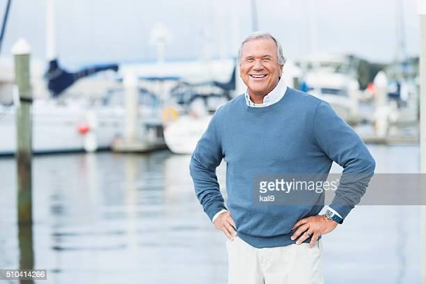 Alter Mann auf Marina, stehend mit Händen auf den Hüften