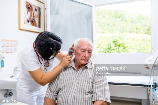 senior man at medical ear check-up - ear exam stock photos and pictures