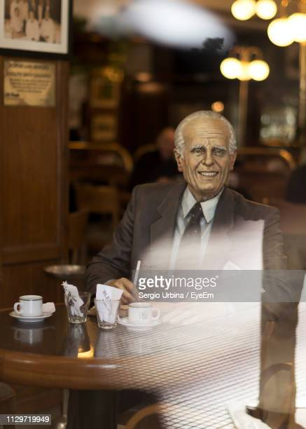 Senior Man At Table Seen Through Cafe Window