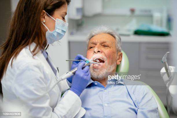 senior man at the dentist - dental equipment stock pictures, royalty-free photos & images
