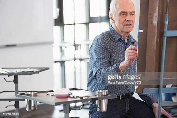 senior man attending painting class - einzelner senior stock-fotos und bilder
