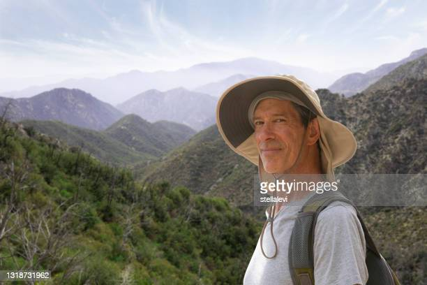 senior man backpacker portrait in the mountains. - stellalevi stock pictures, royalty-free photos & images