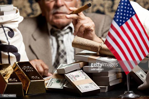 Senior man behind stacks of dollar bills and constitution document