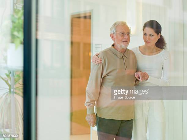 senior man being helped by woman - old man young woman stock photos and pictures
