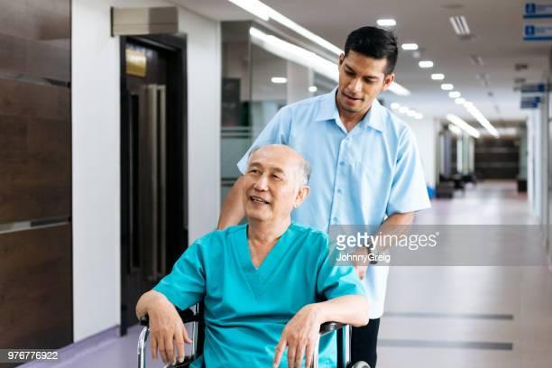 男性看護師が車椅子に押されて年配の男性 - 職業 ポーター ストックフォトと画像