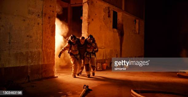 senior man being rescued by firefighters - firefighter stock pictures, royalty-free photos & images