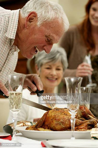 senior man bending over carving roast turkey at dinner table, profile - carving knife stock pictures, royalty-free photos & images
