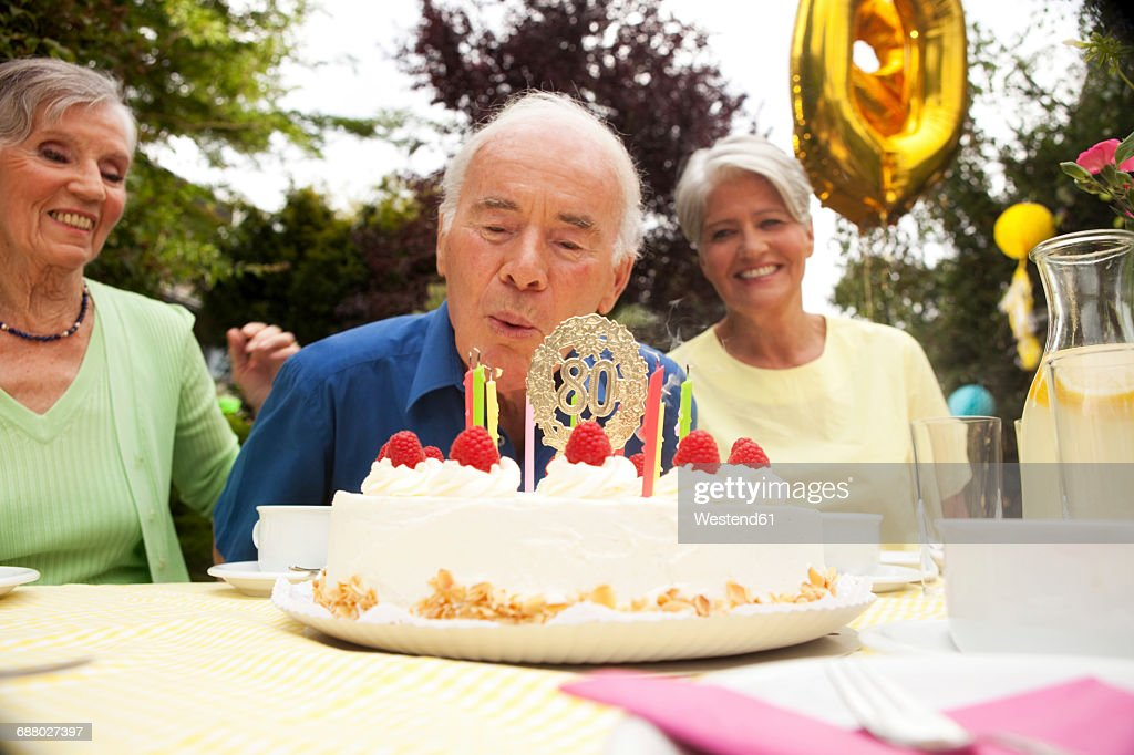 Terrific Senior Man Blowing Candle On 80Th Birthday Cake Stockfoto Getty Personalised Birthday Cards Sponlily Jamesorg